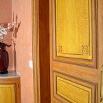 Décor des portes en faux bois imitation citronnier pour les panneaux et les chants en chêne. Mur en stucco antico, couleur rose