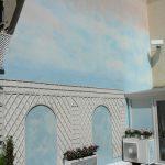Faux ciel sur un mur de jardin agrémenté d'un treillis. Vue d'ensemble